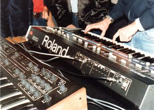 Photo prise lors du NAMM en 1983, montrant les deux synthés branchés l'un avec l'autre. Source : midi.org
